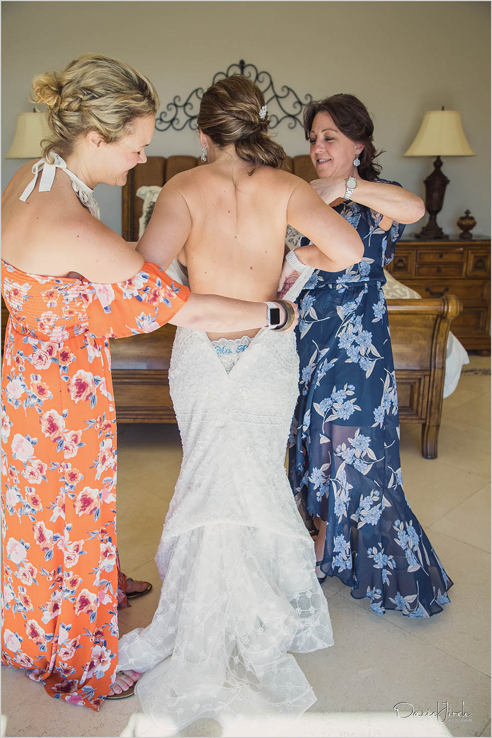 mom and best friend helping bride with the wedding dress