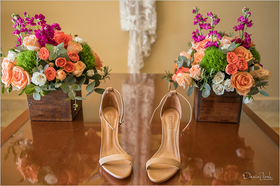 brides shoes with dress in background