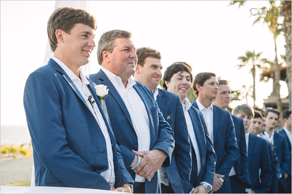 Groom and groomsmen watch bride walk down the aisle