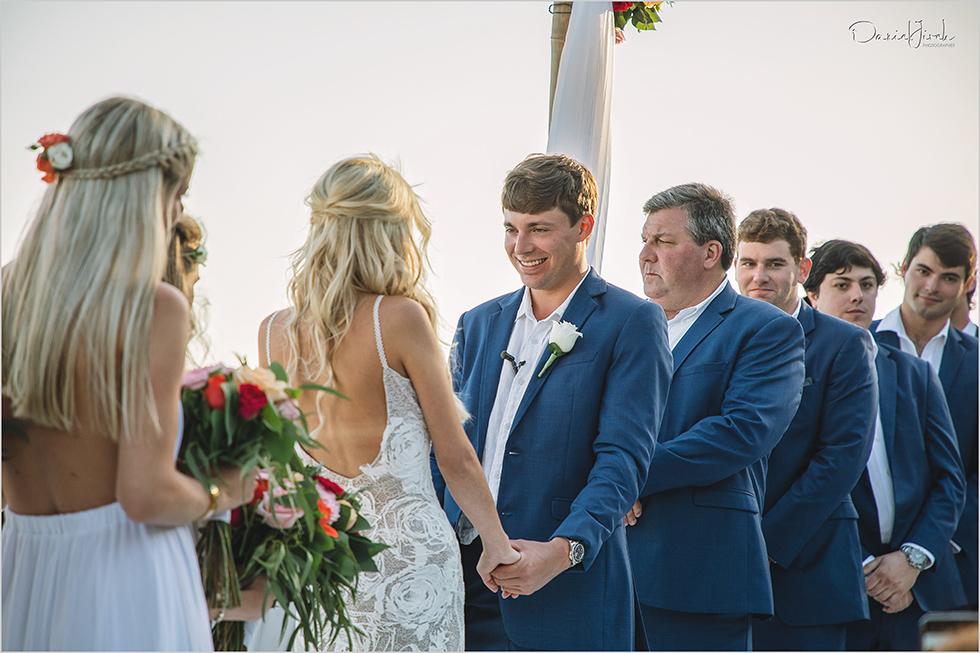 Groom smiles at bride during wedding ceremony in Los Cabos
