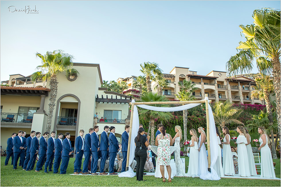 very large bridal party at wedding ceremony on lawn terrace in Los Cabos