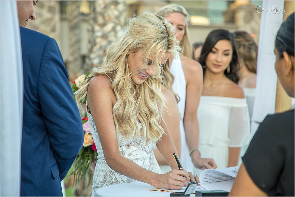 bride signs marriage certificate at Los Cabos wedding ceremony
