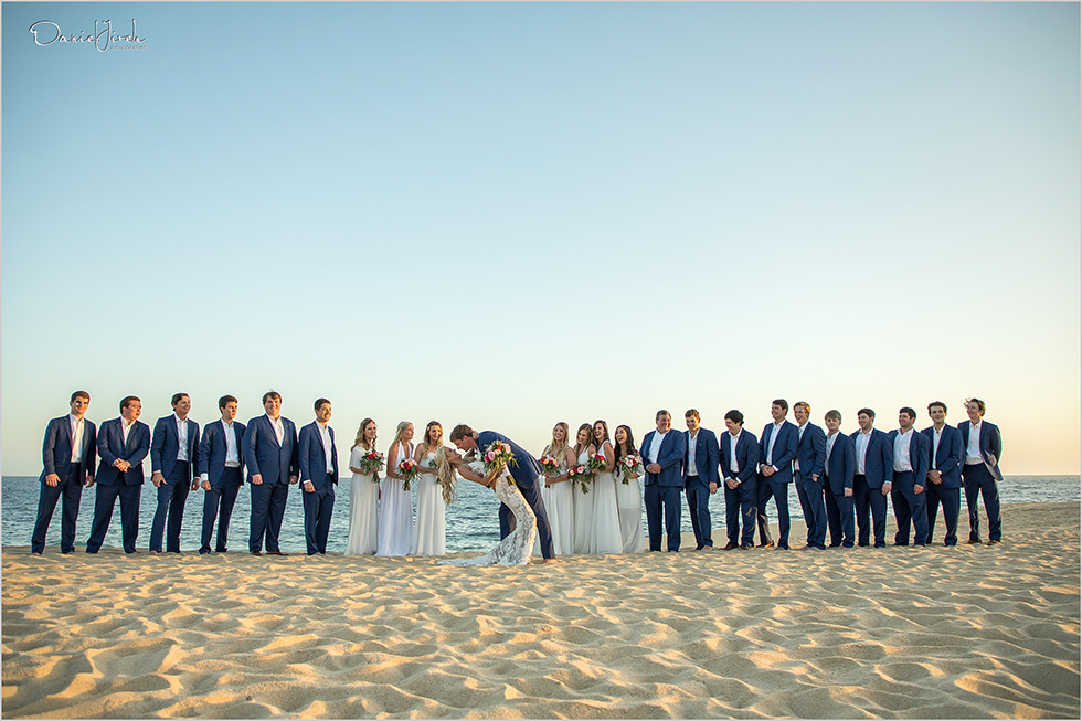 bride and groom kiss in front of bridal party on beach