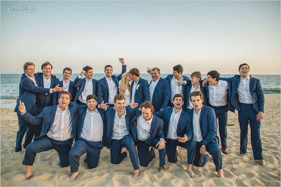 bride and groom kiss in front of groomsmen on the beach