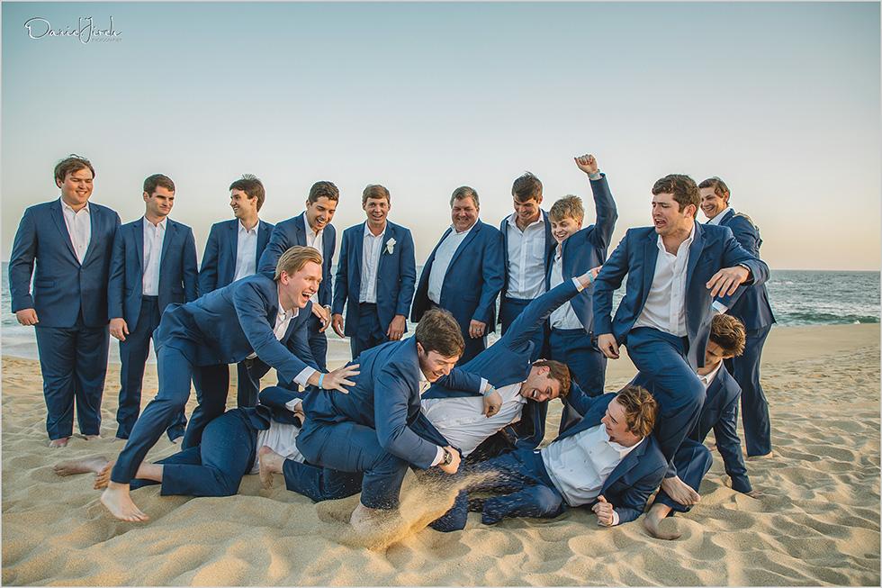 groomsmen wrestle on the beach