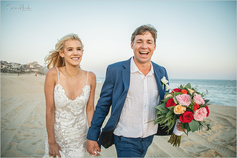 happy bride and groom smiling on beach