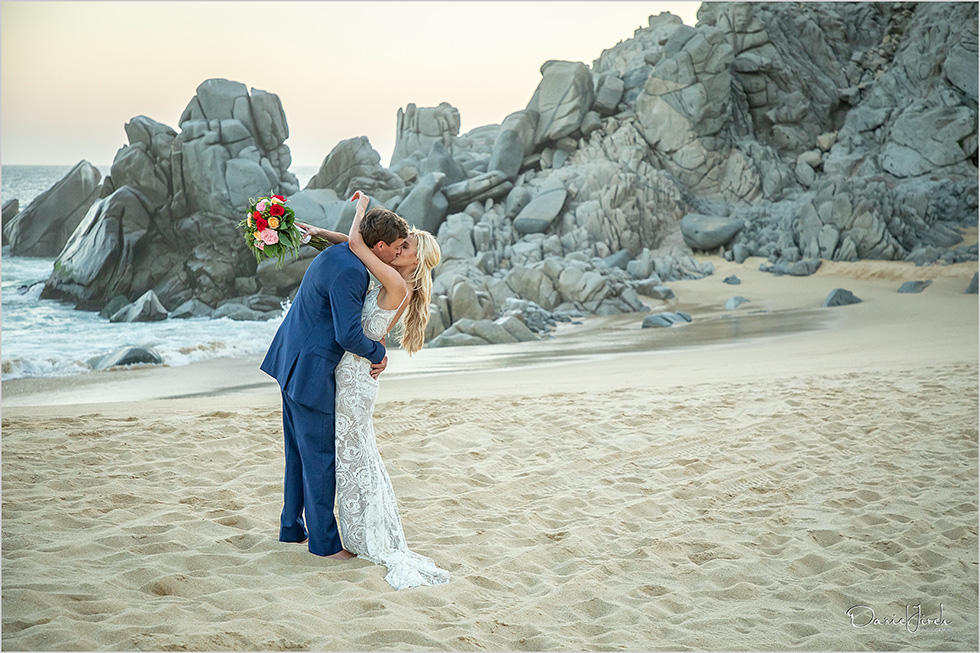 bride and groom kiss on beach with rock formations