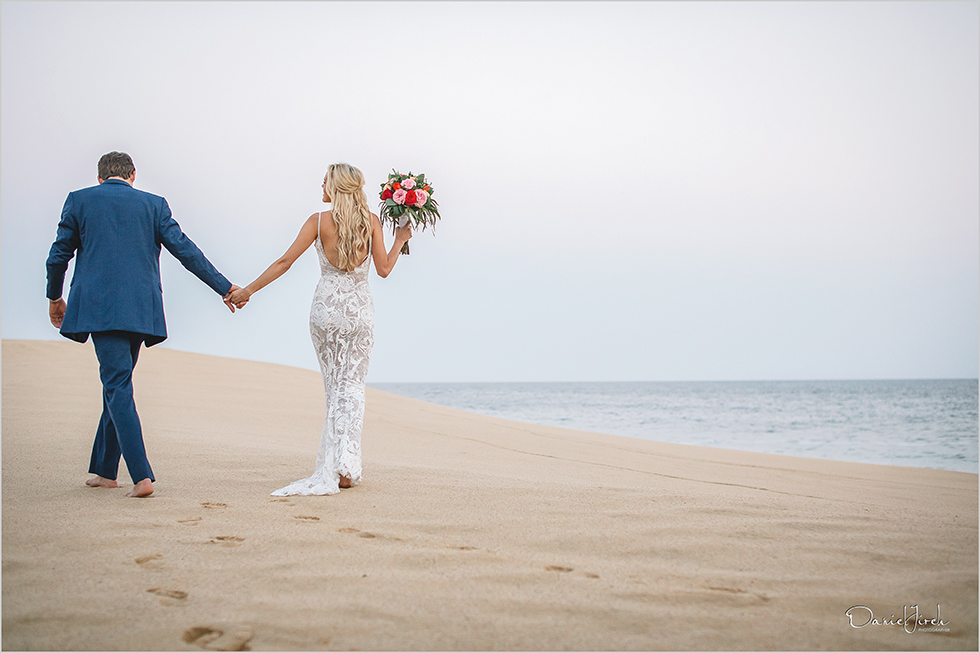 bride and groom holding hands on the beach in Los Cabos