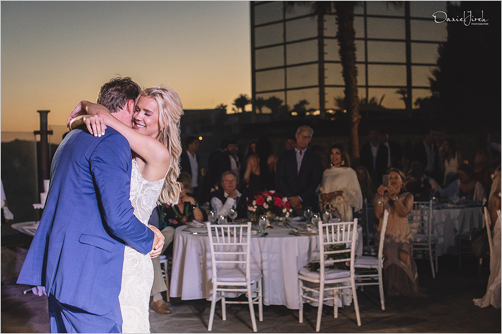 guests watch bride and grooms first dance during sunset at Los Cabos wedding