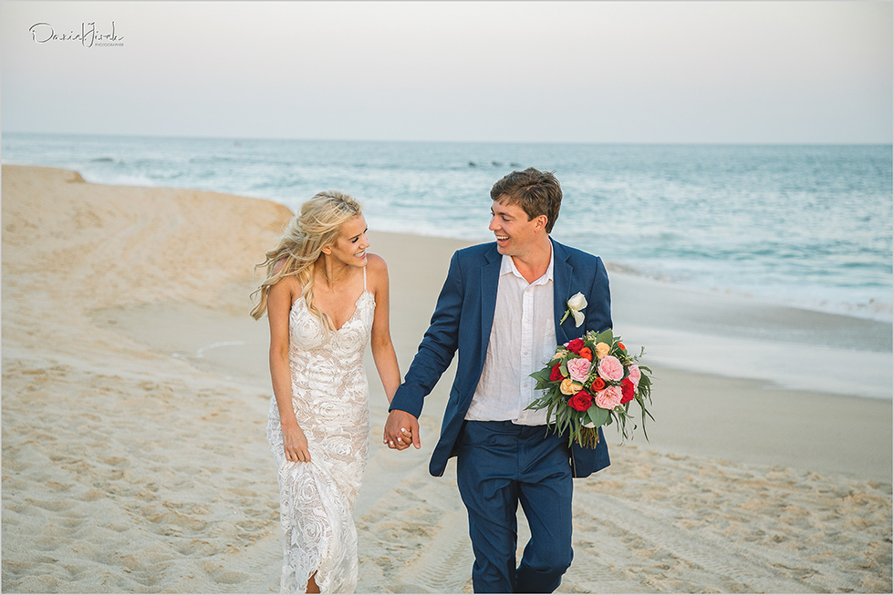 bride and groom laughing and holding hands on the beach in Los Cabos