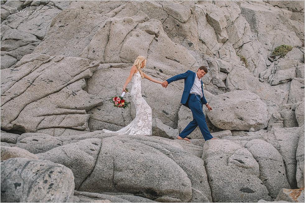 bride and groom walking on rocks in Los Cabos