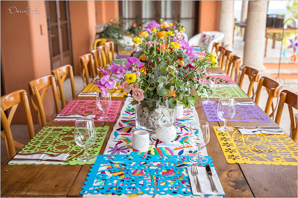 papel picado and colorful flowers decorate Mexican themed tablescape