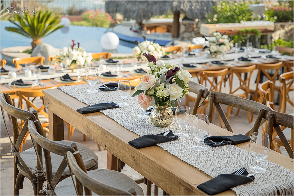 wooden tables, crossback chairs with runners and floral centerpieces