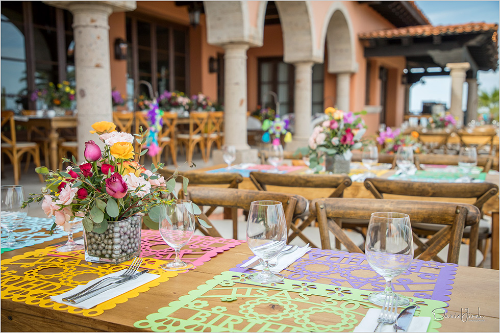 Mexican themed tablescape with bright flowers and papel picado by The Main Event Cabo